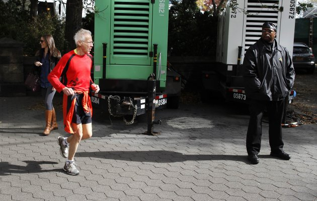 A runner runs past some of the generators that will be used for the NYC Marathon. (Reuters) 