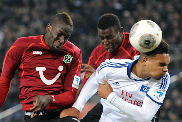 Hamburg's Jonathan Tah , right,  vies for the ball with Hannover's Salif Sane, left,  and Mame Diouf during the German Bundesliga soccer  match between Hamburger SV and Hannover 96 at Imtech Arena in