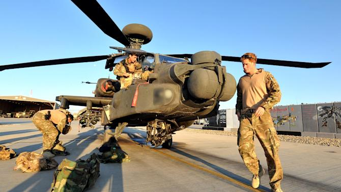 In this photo taken Nov. 1, 2012, made available Monday Jan. 21, 2013 of Britain's Prince Harry or just plain Captain Wales as he is known in the British Army, does a pre-flight check of his Apache Helicopter after starting his 12 hour VHR (very high ready-ness) shift at the British controlled flight-line in Camp Bastion southern Afghanistan, The Ministry of Defense announced Monday that the 28-year-old prince is returning from a 20-week deployment in Afghanistan, where he served as an Apache helicopter pilot with the Army Air Corps. (AP Photo/ John Stillwell, Pool)