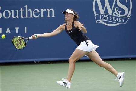 Martina Hingis hits a return during her first round women's doubles match at the Cincinnati Open tennis tournament