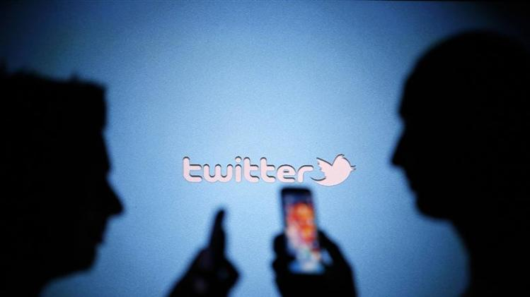 Men are silhouetted against a video screen with a Twitter logo as they pose with Samsung S3 and S4 smartphones in this photo illustration taken in the central Bosnian town of Zenica in this file photo