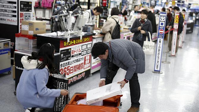 Chinese tourists pack their shopping into a suitcase at a department store in Tokyo