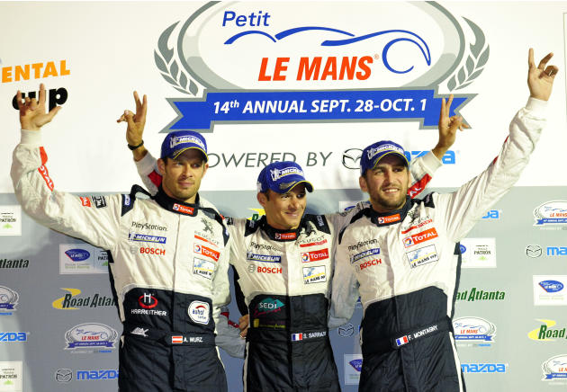 Peugeot drivers, from left, Alexander Wurz, of Austria, Stephane Sarrazin, of France, and Franck Montagny, of France, celebrate on the podium after winning the American Le Mans Series' Petit Le Mans a