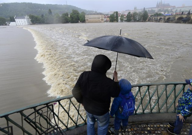 A family watches the swollen Vltava river in the center of Prague, Czech Republic, Sunday, June 2, 2013. Heavy rainfalls cause flooding along rivers and lakes in Germany, Austria, Switzerland and the