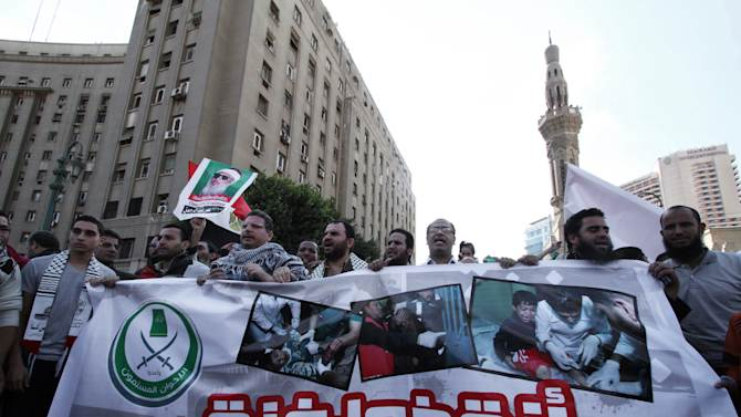 """Egyptian protesters hold a banner with Arabic that reads, """"save Gaza,"""" during a protest in solidarity with Gaza after Israel launched its operation on Wednesday with the assassination of Hamas' top military commander in Cairo, Egypt, Thursday, Nov. 15, 2012. Egypt asked the United States to push Israel to stop its offensive against Hamas militants in the Gaza Strip, warning that the violence could """"escalate out of control,"""" the Foreign Ministry said Thursday. (AP Photo/Ahmed Gomaa)"""