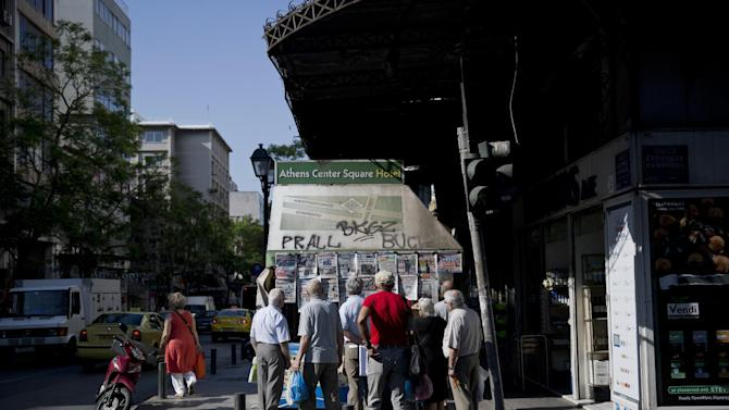 People watch newspapers hanging at a kiosk, in central Athens, on Tuesday, June 30, 2015. The European part of its international bailout expiring Tuesday and with it, any possible access to the remaining rescue loans it contains. As a result, the government is unlikely to repay a roughly 1.6 billion-euro ($1.87 billion) debt to the International Monetary Fund due Tuesday too. (AP Photo/Petros Giannakouris)