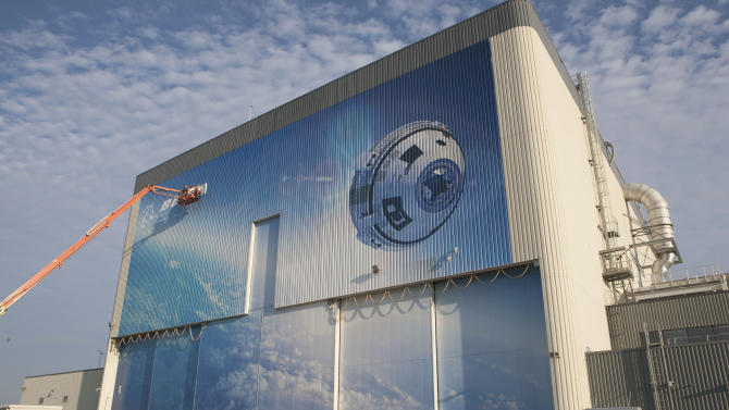 This Friday, Sept. 4, 2015 photo made available by NASA shows a mural depicting Boeing's newly named CST-100 Starliner commercial crew transportation spacecraft on the company's Commercial Crew and Cargo Processing Facility at NASA's Kennedy Space Center in Florida. Friday marked the the grand opening of the facility; the building was formerly a processing site for the space shuttle. (Kim Shiflett/NASA via AP)