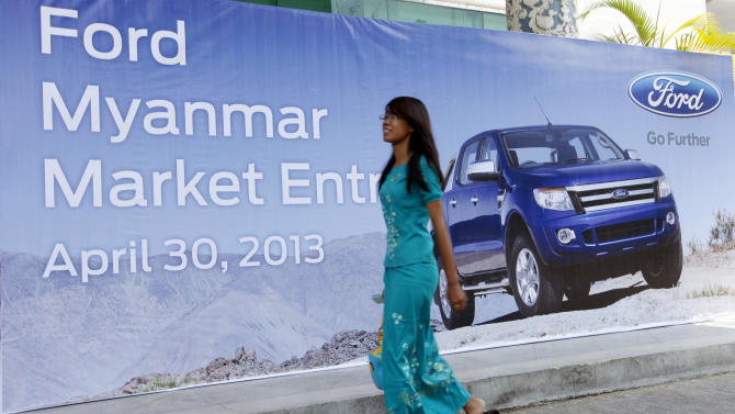 A woman walks past a banner during Ford's launching ceremony Tuesday, April 30, 2013, in Yangon, Myanmar. Ford Motor Co. announced its entry into Myanmar on Tuesday, saying it plans to open the nation's first sales and service showroom for new vehicles by August. (AP Photo/Khin Maung Win)