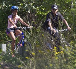 President Barack Obama, and daughter Malia, ride bicycles in Manuel F. Correllus State Forest in West Tisbury,  on Martha's Vineyard, Mass. , Tuesday, Aug. 23, 2011. (AP Photo/Carolyn Kaster)