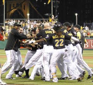 Pittsburgh Pirates' Drew Sutton, center, is surrounded by his team in the bottom of the ninth inning of the baseball game after hitting the game winning home run to lift the Pirates to an 8-7 win over the Houston Astros on Tuesday, July 3, 2012, in Pittsburgh. (AP Photo/Keith Srakocic)
