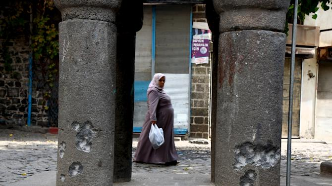 A woman walks past columns of a historical 16th-century minaret badly damaged by gunfire earlier this week, in the Kurdish dominated southeastern city of Diyarbakir