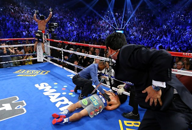 LAS VEGAS, NV - DECEMBER 08:  Manny Pacquiao lays face down on the mat after being knocked out in the sixth round as Juan Manuel Marquez celebrates during their welterweight bout at the MGM Grand Garden Arena on December 8, 2012 in Las Vegas, Nevada.  (Photo by Al Bello/Getty Images)