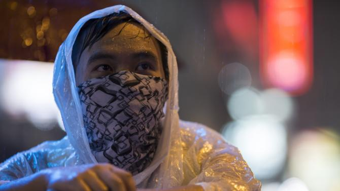 A pro-democracy protester stands by a barricade during heavy rain at the Mongkok shopping district of Hong Kong