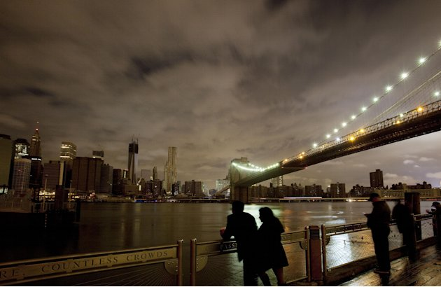 People stop along the Brooklyn waterfront to look at the Brooklyn Bridge and the Manhattan skyline, Tuesday, Oct. 30, 2012 in New York. Much of lower Manhattan is without electric power following the