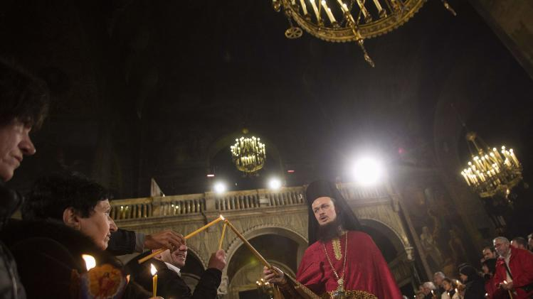 "Worshippers reach to light their candles with ""holy fire"" from the candles of a priest, during an Orthodox Easter service at Alexander Nevski cathedral in Sofia"