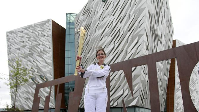ADD CREDIT - Karen Marshall, the first torch bearer from Northern Ireland, poses with the Olympic torch at Titanic Museum, before the relay in Belfast, Northern Ireland, Sunday, June 3, 2012.  (AP Photo/Peter Morrison)