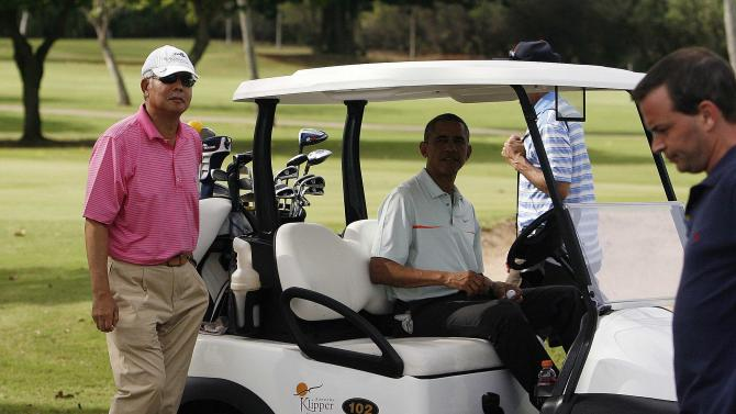 U.S. President Barack Obama and Malaysia's Prime Minister Najib Razak get in their golf cart after playing on the 18th green in Kaneohe