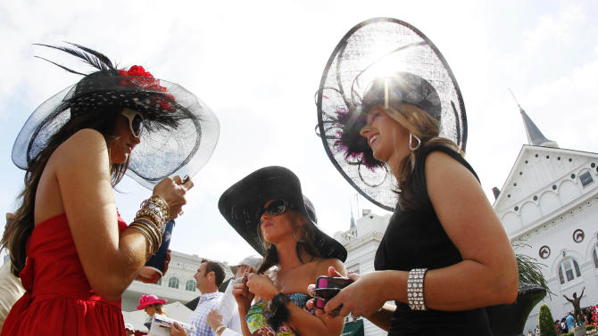 From left, Amanda Lear, from Ruby, S.C., Amada Griffo, of Wapakoneta, Ohio, and Sara Coucher, of Frederickstown, Ohio, chat in the paddocks before the 138th Kentucky Derby horse race at Churchill Downs, Saturday, May 5, 2012, in Louisville, Ky. The Run for the Roses draws them to Churchill Downs. But what race goers wear is as much a spectacle in itself. (AP Photo/Mark Humphrey)