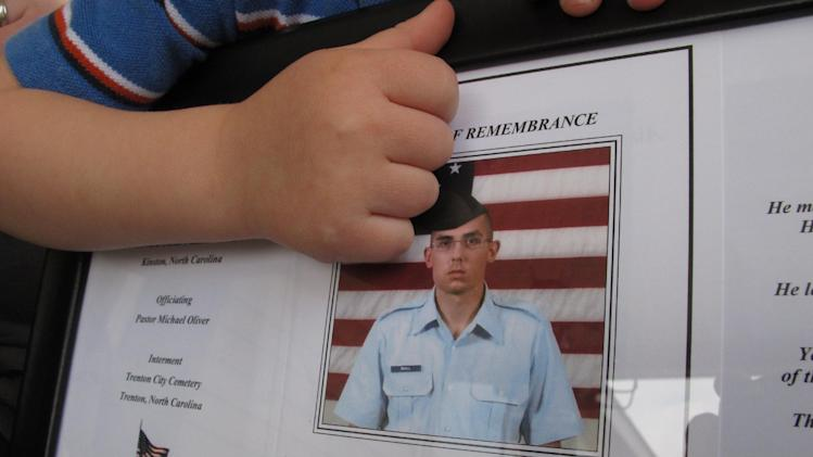 Shane Mercer points to a photo of his father, Airman Will Small, at his Kinston, N.C., home on Monday, March 18, 2013. Will Small died of rabies, and people who received his donated organs became sick, and one has died. (AP Photo/Allen Breed)