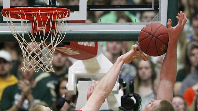 New Mexico center Alex Kirk, left, blocks a shot by Colorado State center Colton Iverson in the first half of an NCAA basketball game in Fort Collins, Colo., on Saturday, Feb. 23, 2013. (AP Photo/David Zalubowski)