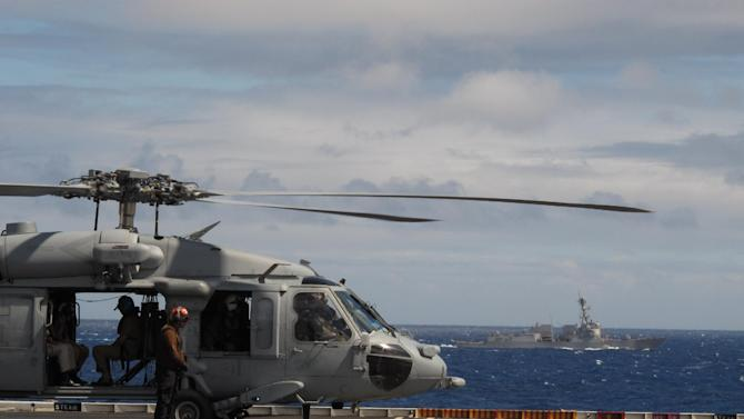 A U.S. Navy helicopter prepares to take off from the USS Nimitz aircraft carrier while destroyer USS Chafee travels alongside on Wednesday, July 18, 2012.  The U.S. Navy is using its Rim of the Pacific exercises to test whether aircraft and sea vessels run the same using fuels made up of biofuel blends rather than traditional petroleum. (AP Photo/Oskar Garcia)