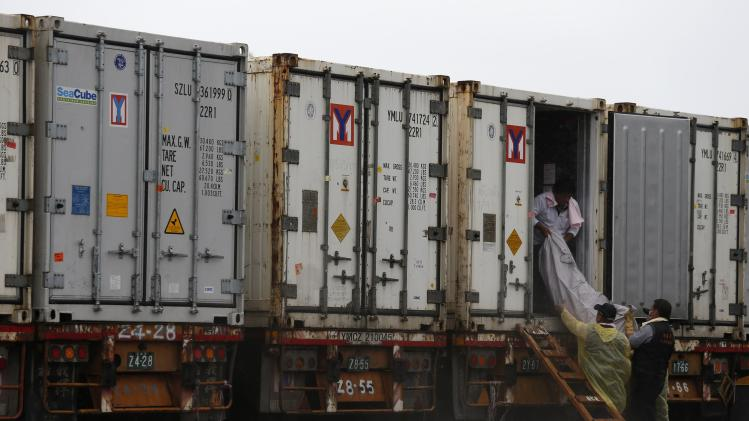 Body of a passenger who died in a TransAsia Airways plane crash is carried from inside a container with cooling facilities at a funeral parlor on Taiwan's offshore island of Penghu