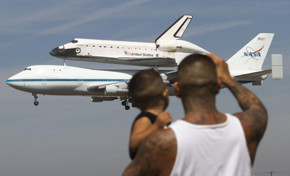 Spectators Mario Vasquez, 40, of Redondo Beach and his son Mario Jr., 2, watch as space shuttle Endeavour, atop NASA's Shuttle Carrier Aircraft, prepares to land at Los Angeles International Airport in Los Angeles, on Friday, Sept. 21, 2012.  (AP Photo/Ringo H.W. Chiu)