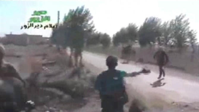 In this amateur video provided by a group which calls itself Ugarit News, Syrian rebels cross a road during a raid on the village of Hatla, Syria, Wednesday, June 12, 2013. On Wednesday, activists said Syrian rebels battled Shiites in Hatla, in the country's east, killing more than 60 people, including civilians. The content has been authenticated based on its translation and content has been checked by regional experts against known locations and events, and is consistent with independent Associated Press reporting. (AP Photo/Amateur video via Ugarit News)