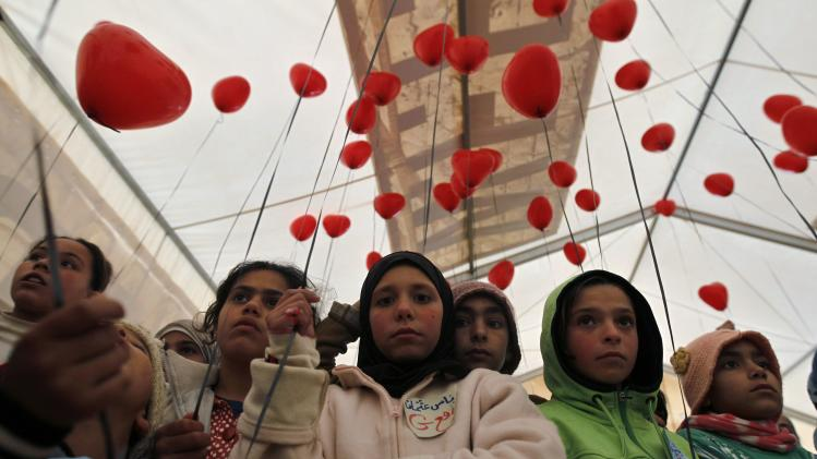 Young Syrian refugees prepare to release red balloons at Al Zaatari Syrian refugee camp in Mafraq