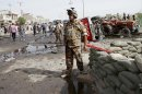 Iraqi security force members inspect the site of a car bomb attack in Basra, 340 miles (550 kilometers) southeast of Baghdad, Iraq, Monday, May 20, 2013. Two car bombings in the southern city of Basra, killing and wounding dozens of people, police said. Iraq has seen a spike of attacks, including bombings hitting both Sunni and Shiite civilian targets over the last week. (AP Photo/ Nabil al-Jurani)