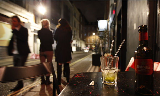 Two young women smoke outside a bar in the central London area of Soho late Friday, April, 21, 2012.  Binge drinking has reached crisis levels in Britain, health experts say, costing the cash-strapped