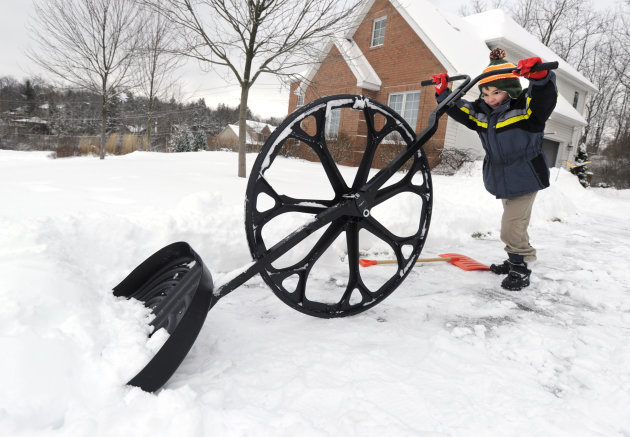 "Nathan Lee, 5, uses a ""wovel"" to remove snow from his driveway along Megan Drive, in State College, Pa. A major winter storm hit Centre County Wednesday and the clean up continues Thursday, Dec. 27, 2"