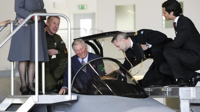 Britain´s Prince Charles is getting acquainted with Swedish fighter plane JAS Gripen while Prince Carl Philip of Sweden (R) and Brigadier General Johan Svensson (second from right) and Camilla, Duchess of Cornwall, (L) looks on at the Arlanda Airport in Stockholm, Sweden, March 22, 1012. The British Royal Couple are in Sweden for an official visit. (AP Photo/Scanpix, Anders Wiklund)   SWEDEN OUT