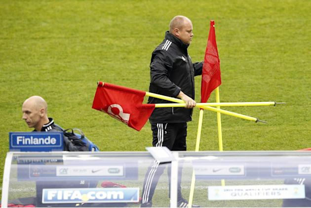 Finland's soccer head coach Mixu Paatelainen carries flags during a training session at the Stade de France stadium in Saint Denis, north of Paris, Monday, Oct. 14, 2013, ahead of their 2014 World Cup