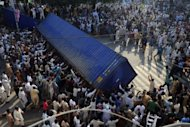 Pakistani Muslim demonstrators topple a freight container, placed by police to block a street, during a protest against an anti-Islam film in Lahore. Violent demonstrations in Pakistan left at least 17 people dead and hundreds injured as fresh protests erupted across the Muslim world against a US-made film and French cartoons mocking Islam