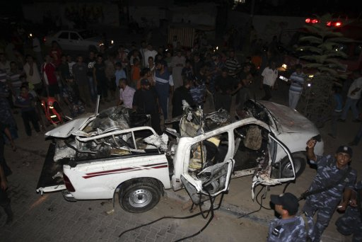 Palestinians look at destroyed vehicle following an Israeli air strike in Rafah