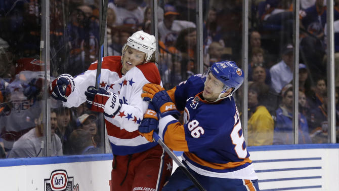 New York Islanders' Nikolay Kulemin, right, checks Washington Capitals' John Carlson into the boards during the second period of Game 3 of a first-round NHL hockey playoff series Sunday, April 19, 2015, in Uniondale, N.Y. (AP Photo/Seth Wenig)