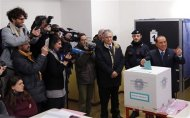 Former Prime Minister Silvio Berlusconi gestures as he casts his vote at the polling station in Milan, February 24, 2013. Italians began voting on Sunday in one of the most closely watched elections in years, with markets nervous about whether it can produce a strong government to pull Italy out of recession and help resolve the euro zone debt crisis. REUTERS/Stefano Rellandini