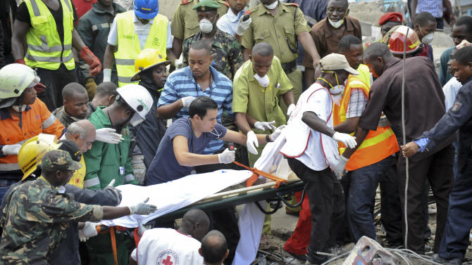 Rescuers from the Tanzania Red Cross carry away a body from the rubble of a collapsed building in downtown Dar es Salaam, Tanzania Friday, March 29, 2013. A Tanzanian police official says the multi-storey building was in the final stages of its construction and most of the people caught up in the collapse were passing by. (AP Photo/Khalfan Said)