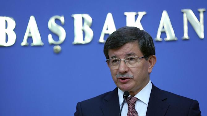 FILE - Turkey's new Prime Minister Ahmet Davutoglu announces his cabinet ministers in Ankara, Turkey, in this Aug. 29, 2014 file photo. Davutoglu says 49 Turkish hostages held by Islamic militants have been freed. Davutoglu said the group was released early on Saturday Sept. 20, 2014 and had arrived in Turkey. (AP Photo/Burhan Ozbilici, File)