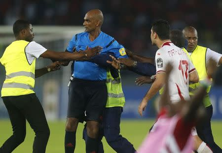 Referee Rajindraparsad Seechurn is surrounded by security as players of Tunisia confront him after losing their quarter-final soccer match of the 2015 African Cup of Nations against Equatorial Guinea in Bata