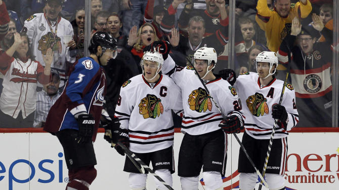 As Colorado Avalanche defenseman Ryan O'Byrne, left, looks on, Chicago Blackhawks center Jonathan Toews, second from left, is congratulated after scoring a goal by teammates Brandon Saad, third from left, and Duncan Keith in the first period of an NHL hockey game in Denver, Friday, March 8, 2013. (AP Photo/David Zalubowski)