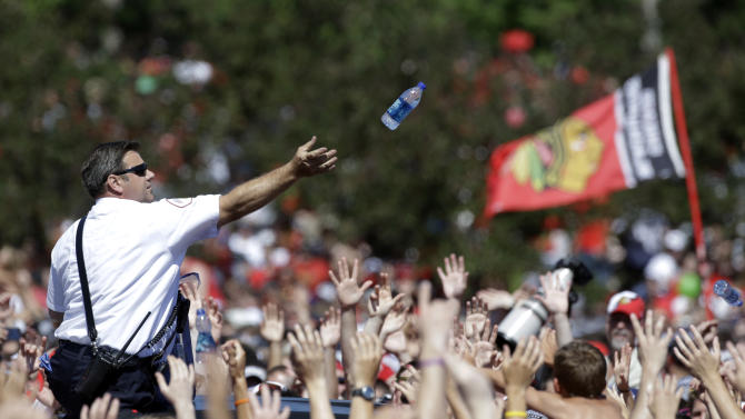 A police officer throws water bottles to fans as thousands gather in Grant Park for a rally to honor the NHL Stanley Cup hockey champion Chicago Blackhawks, Friday, June 28, 2013, in Chicago. (AP Photo/M. Spencer Green)