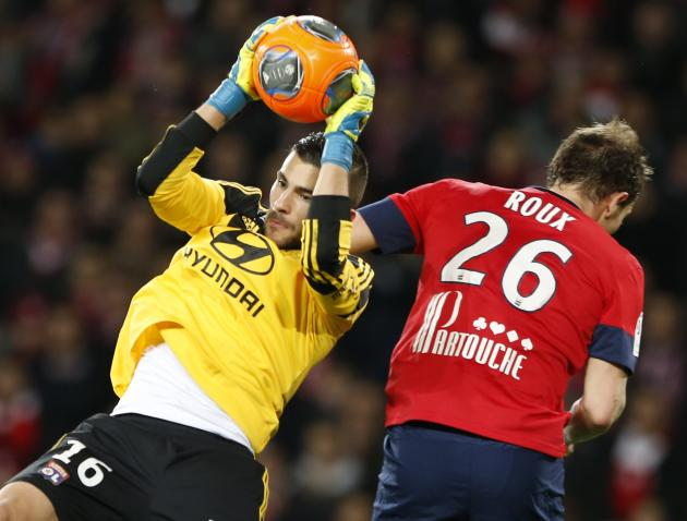 Lille's Roux fights for the ball with Lyon's goalkeeper Lopes during their French Ligue 1 soccer match at Pierre Mauroy Stadium in Villeneuve d'Ascq