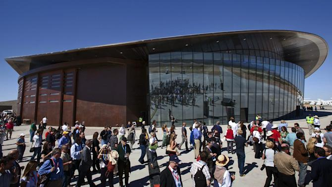 """FILE - In this Oct. 17, 2011 file photo, guests stand outside the new Spaceport America hangar in Upham, N.M.   Gov. Susana Martinez Tuesday May 7,2013 announced that Elon Musks' Space Exploration Technologies, or SpaceX, has signed a three-year lease to do testing of its """"Grasshopper"""" reusable rocket in southern New Mexico, adding a second company at Spaceport. (AP Photo/Matt York, File)"""