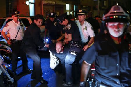 NYPD officers carry a protester detained after a fight during a march in support of the protests against the killing of unarmed black teenager Michael Brown in Ferguson, Missouri, in Manhattan, New York