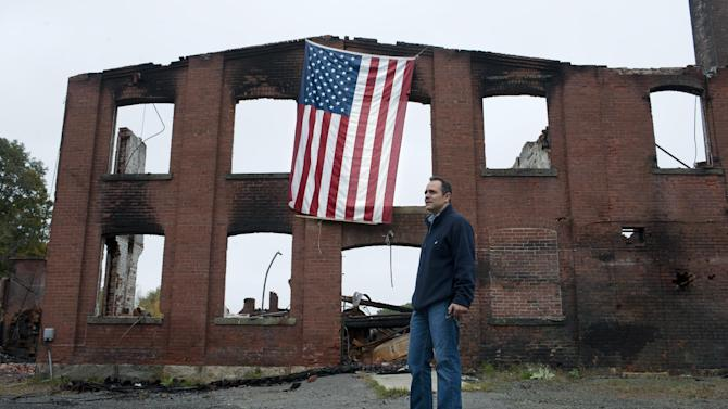 """Matt Bevin stands at the site of his family's factory destroyed by fire in East Hampton, Conn., Wednesday, Oct. 3, 2012. The 180-year-old New England company that made the tiny bell that tinkles every time an angel gets its wings in the holiday classic """"It's a Wonderful Life"""" is resuming production months after the factory was destroyed in a fire. (AP Photo/Jessica Hill)"""