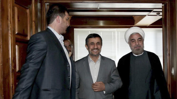 In this photo released by the official website of the Iranian presidency office, outgoing Iranian President Mahmoud Ahmadinejad, center, and President-elect Hasan Rowhani, right, make their way during their meeting at Rowhani's office in Tehran, Iran, Tuesday, June 18, 2013. (AP Photo/Presidency Office, Ebrahim Seyyedi)