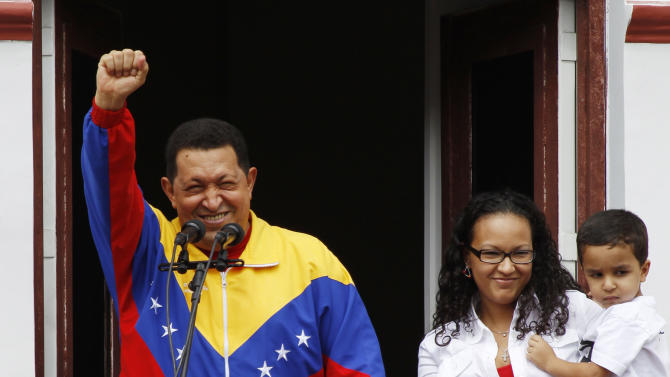 """FILE - In this May 22, 2011 file photo, Venezuela's President Hugo Chavez greets supporters next to his daughter Maria and grandson Jorge after his radio and television program """"Hello President!,"""" his first public appearance after injuring himself while jogging two weeks earlier, at Miraflores presidential palace in Caracas, Venezuela. Venezuela's Vice President Nicolas Maduro announced on Tuesday, March 5, 2013 that Chavez has died.  Chavez, 58, was first diagnosed with cancer in June 2011.  (AP Photo/Fernando Llano, File)"""