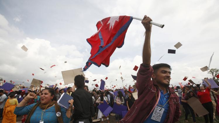 A Nepalese holds high the Nepalese national flag, as others celebrate after participating in an attempt to break the record for the largest human national flag, in Katmandu, Nepal, Saturday, Aug. 23, 2014. One of the organizers, Ashish Chaulagai, said more than 38,000 people were estimated to have formed Nepal's flag, shaped as two red triangles with a blue border. Nepal is the only country whose flag is not quadrilateral. The last record was set in Pakistan by 28,957 people. (AP Photo/Bikram Rai)